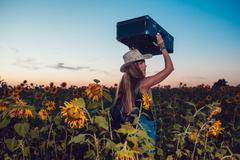 Girl in a cowboy hat standing with a suitcase on the road in the sunflower field Stock Photos