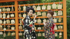 2 Japanese Women in front of Ema wooden plaques in Shrine Stock Footage