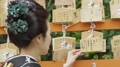 A Japanese Woman in front of Ema wooden plaques in Shrine Stock Footage