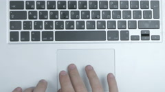 Top view of laptop computer keyboard and touch-pad used by male hands. Close up Stock Footage