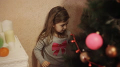 Two smiling little girls decorating Christmas decorations on New Year tree at Stock Footage