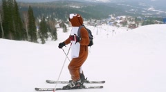 Son and father skiers on the slope at a ski resort wear kigurumi suits in Stock Footage