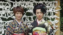 2 Japanese Women in Traditional Kimono tying o-mikuji paper strips Stock Footage