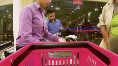 Supermarket: Employees checkout items with bachelor shopper nearby Stock Footage