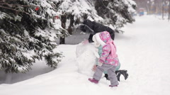 Mom and daughters sculpts snowman Stock Footage