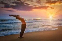 Young sporty fit man doing yoga Sun salutation Surya Namaskar Stock Photos