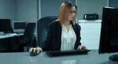4K: A secretary is working at a computer in her office Stock Footage