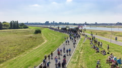 Crowd of people walking on a dyke along a river, Netherlands, 4K time lapse Stock Footage
