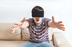 Young man is fascinated from virtual reality headset. Stock Photos