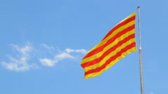 Catalunya flag waving in slow motion against clean blue sky Stock Footage