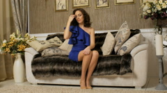 Brunette with curly hair medium length, sitting on sofa, touching her hair and Stock Footage