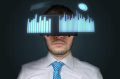Young businessman is wearing 3D virtual reality headset. Statistic graphs and Stock Photos