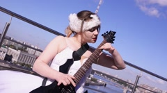 Girl in ballerina white suit play electric guitar on seafront in sunny day Stock Footage