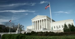 The US Supreme Court wide with flags and blue sky with light clouds Stock Footage