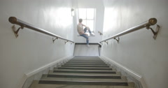 Young man sits in stairwell window then walks up stairs 4K Stock Footage