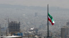 Iranian waving flag in the middle of polluted capital city of Tehran Stock Footage