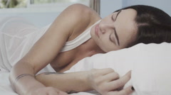 Beautiful young brunette waking up peacefully while lying on her bed Stock Footage