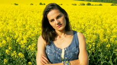 Serious woman standing on rapseed's field, steadycam shot, slow motion shot at 2 Stock Footage