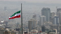 Iranian flag waving in wind in the middle of Tehran capital city of Iran Stock Footage
