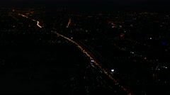 Aerial view of long line of cars moving in highway traffic - metropolis at night Stock Footage