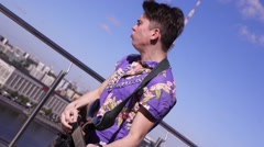 Man in scotland skirt, shirt play electric guitar on seafront in sunny day Stock Footage