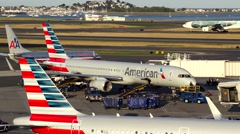 American Airlines airplane at airport terminal gate, ground crew Stock Footage