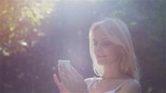 Beautiful Girl Using SmartPhone Enjoying the Sun in City Park. Stock Footage