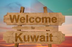 Welcome to Kuwait sign on wood background with blending national flag Stock Photos