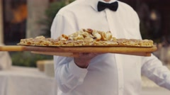 A young waiter in the restaurant serving banquet, delivers delicious. Stock Footage