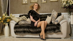 Slim blonde sitting on fashionable couch, fan blowing, hair and dress are waving Stock Footage