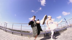Man in skirt play electric guitar on seafront in dance cancan with girl in Stock Footage
