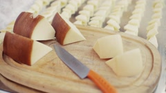 Cut slices of fresh parmesan cheese on a wooden plate. Sharp knife. Stock Footage