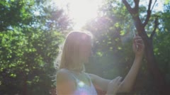 Beautiful Girl Making Selfie Enjoying the Sun in City Park. Stock Footage