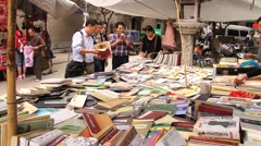 People choose used books from the stall at the shopping street in Xian, China. Stock Footage