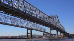 Cargo ships and other boats travel under the Crescent City Bridge with New Stock Footage