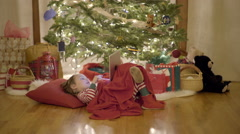 Happy Boy Eats A Candy Cane And Plays With His Tablet Under A Christmas Tree Stock Footage