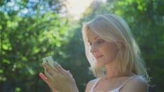 Beautiful Girl Using SmartPhone Enjoying the Sun in City Park. Stock Footage