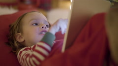 Closeup Of Little Boy Eating A Candy Cane And Playing A Game On His Tablet Stock Footage