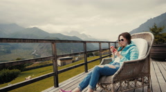 Woman tourist dressed in stylish clothes shoots video of beautiful mountain Stock Footage
