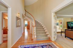 Bright beige hallway interior with carpet staircase in large luxury house. No Stock Photos