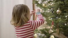 Happy Child Walks Into Frame, Hangs A Bell Ornament On Christmas Tree, Exits Stock Footage