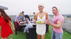 4K Happy group of young friends enjoying a rooftop barbecue in the city Stock Footage