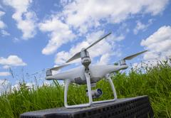 Quadrocopters on a plastic box in the grass Stock Photos