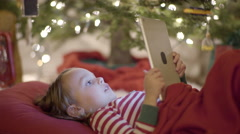 Little Boy Intently Watching A Video On His Tablet Underneath A Christmas Tree Stock Footage