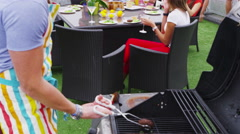 4K Portrait of a happy young man cooking barbecue for his friends Stock Footage