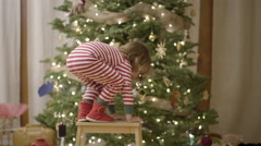 Child Hangs A Candy Cane Decoration On A Christmas Tree, Then Runs Toward Camera Stock Footage