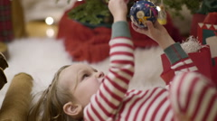 Little Kid, Underneath Christmas Tree, Hangs An Ornament Stock Footage