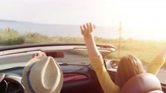 Fun Young Couple In A Convertible Cabriolet Car Driving By The Beach Taking Stock Footage