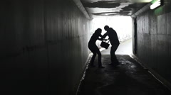 Man thief ambush and steals a bag from a woman in a dark tunnel Stock Footage