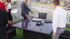 4K Attractive mixed ethnicity business team in open air meeting with city views Stock Footage